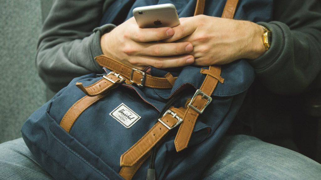 Person mit Rucksack und Handy