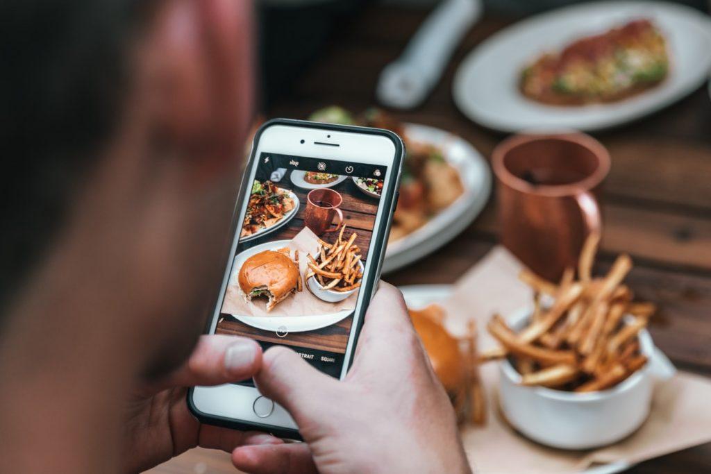 Mann fotografiert Burger mit dem Handy