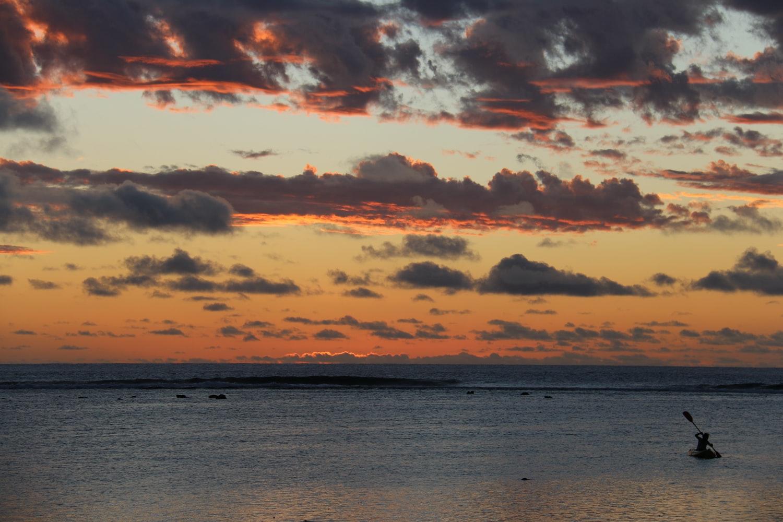 Mensch paddelt im Sonnenuntergang vor Mangaia Cookinseln