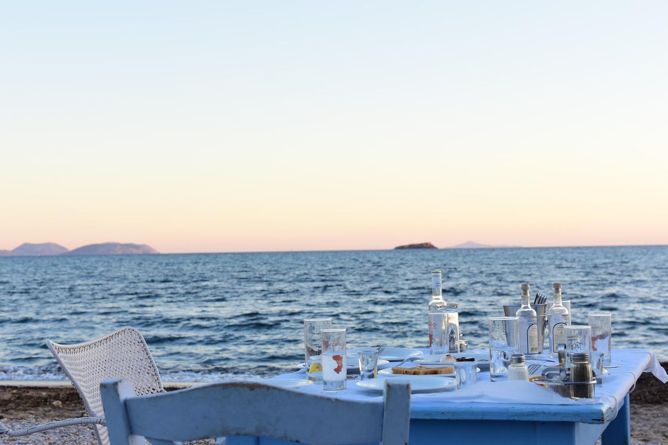 Gedeckter Tisch und Ouzoflasche am Strand in Rhodos Griechenland