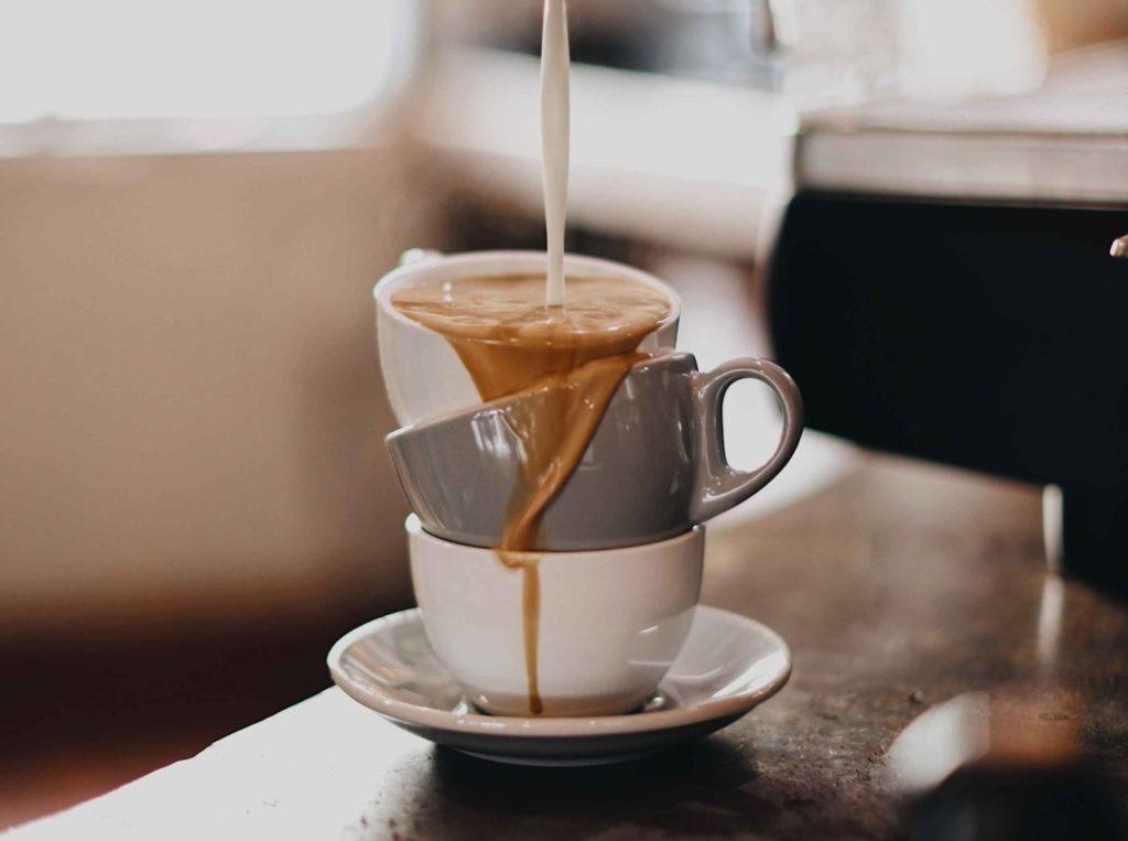 Kaffee läuft über gestapelte Tassen