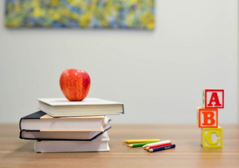 Apfel mit Schulbücher und Stiften auf Schreibtisch
