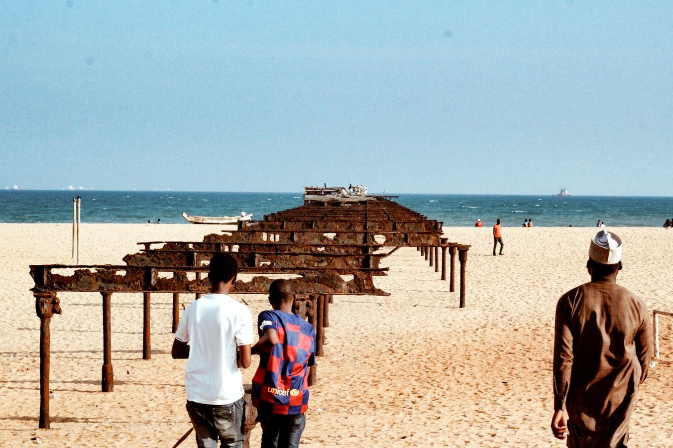 Rostiger Pier am Strand in Togo